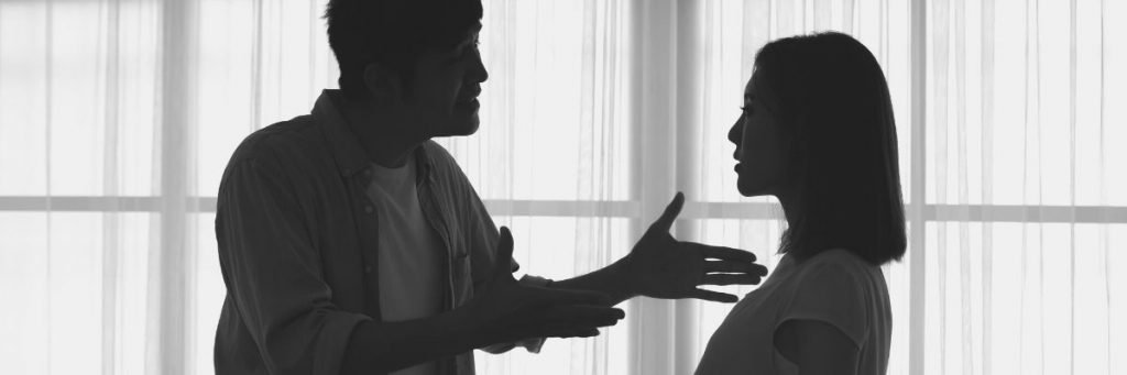 A black and white image represents a discussion between a couple before start Family violence
