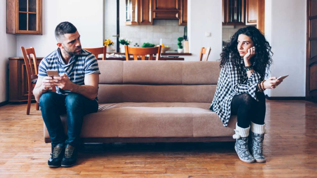 A couple in the living room looks to getting a divorce or separation. They are looking at each other, seemings upset. Divorce Lawyer. separation and divorce